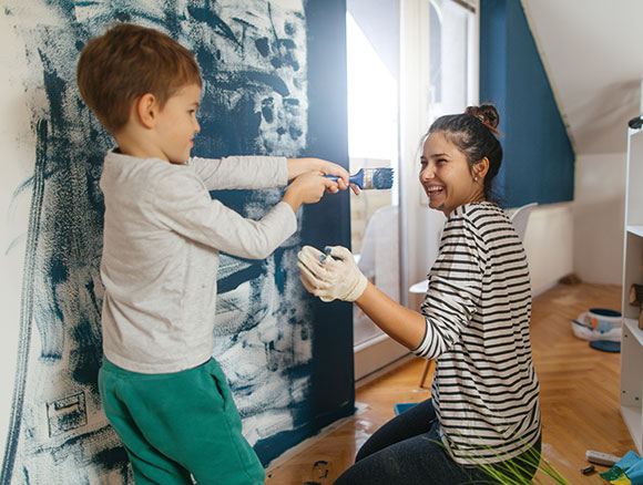 boy and woman painting room