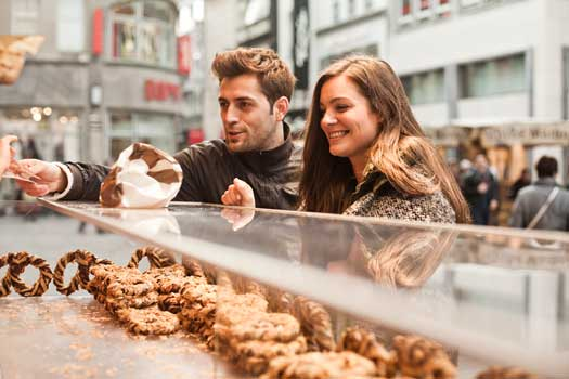 Man and woman at a bakery buying some pastries.