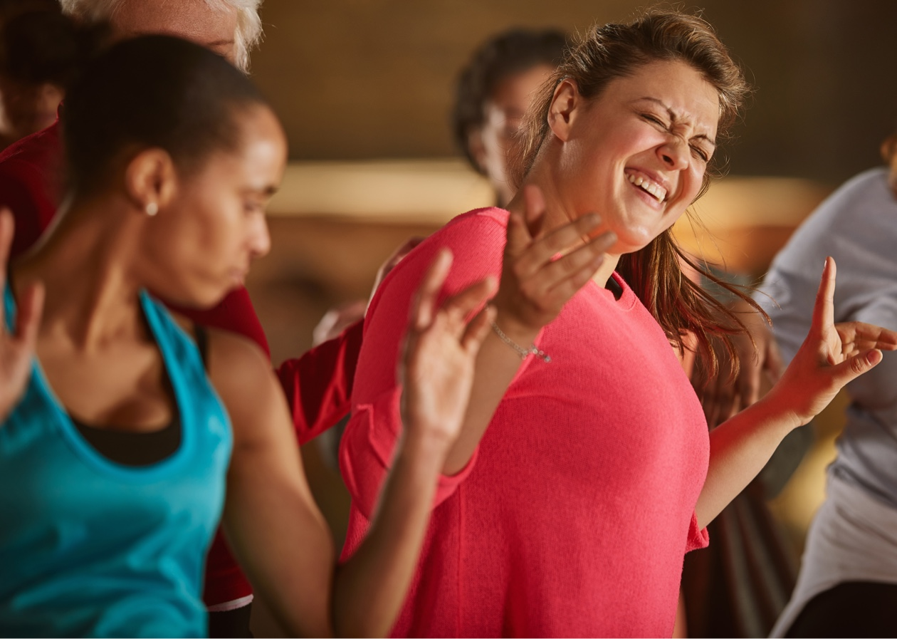 woman in coral top enjoying fitness class
