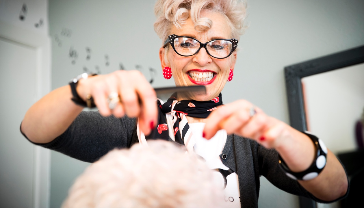 woman in glasses cutting man's hair