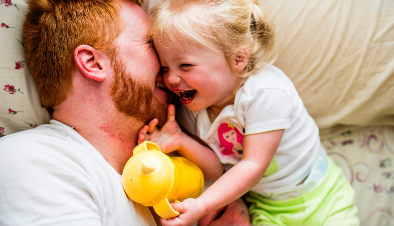 dad and daughter laughing in bed