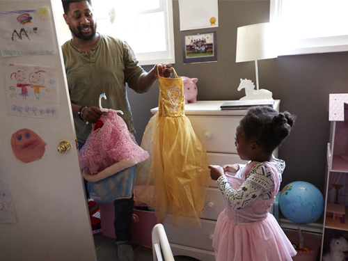 Father helping his daughter pick a costume.
