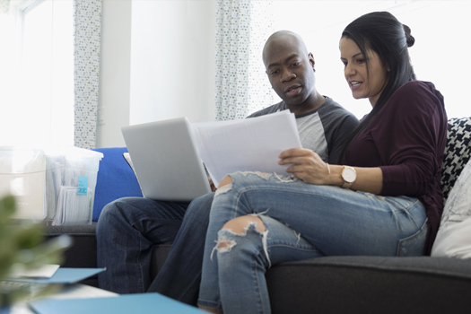 A couple sitting on the couch looking at paperwork together.