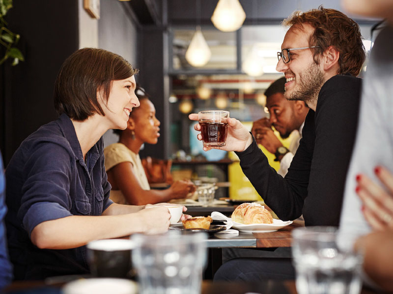 Two people sitting in a resturant smiling at each other.