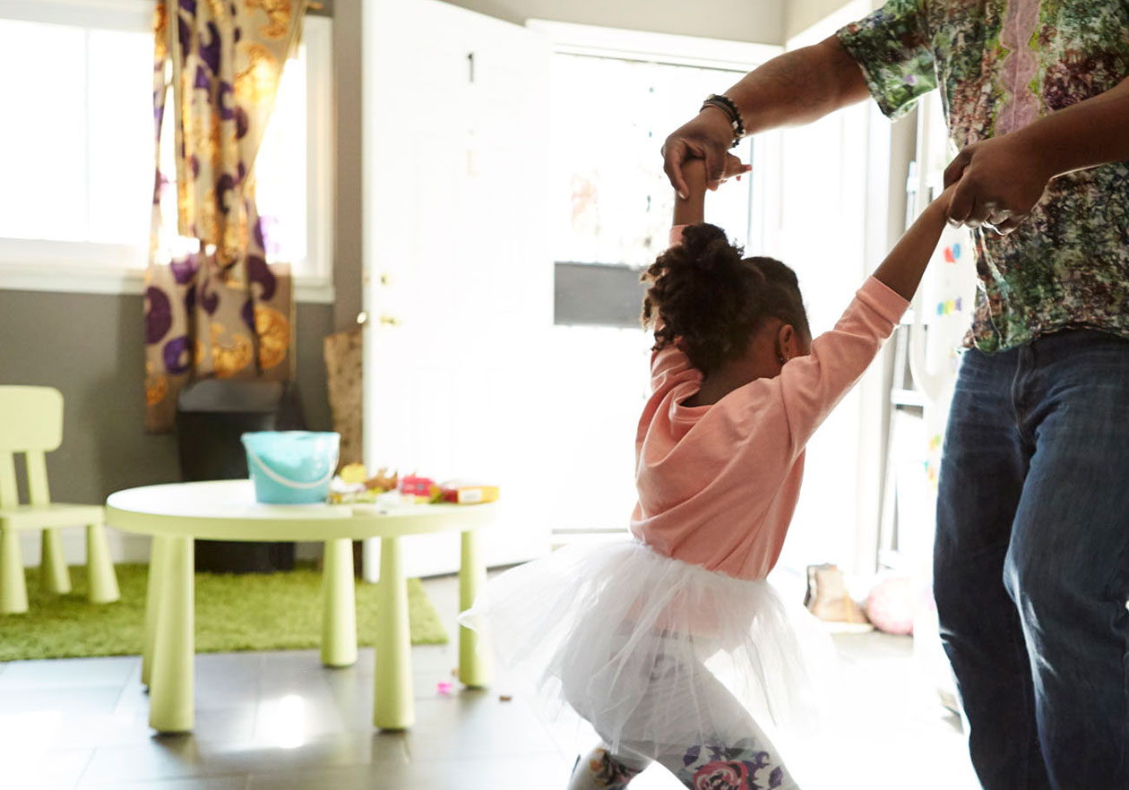 Father and daughter dancing in the kitchen