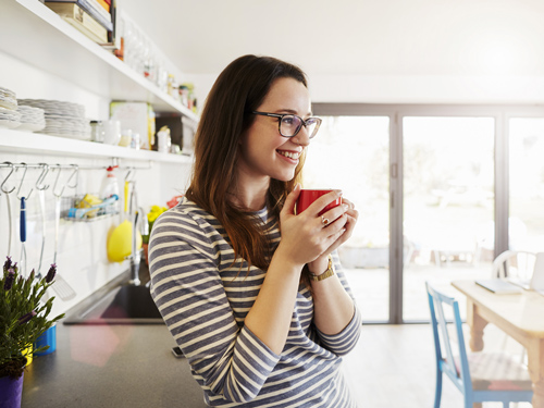 A smiling woman with glasses hodling a red mug