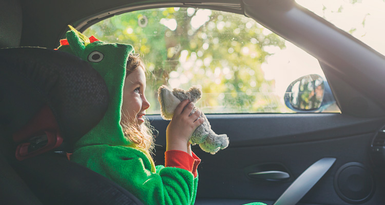 Girl in the passenger seat of the car with a toy in her hand.