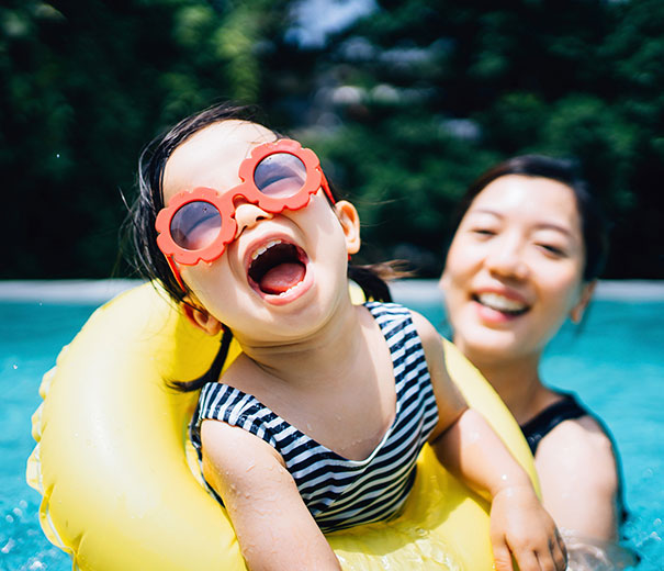 A girl in the pool wearing sunglasses
