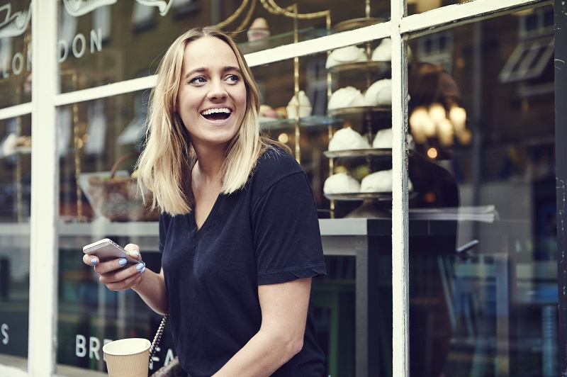 Girl with a mobile and coffee, laughing