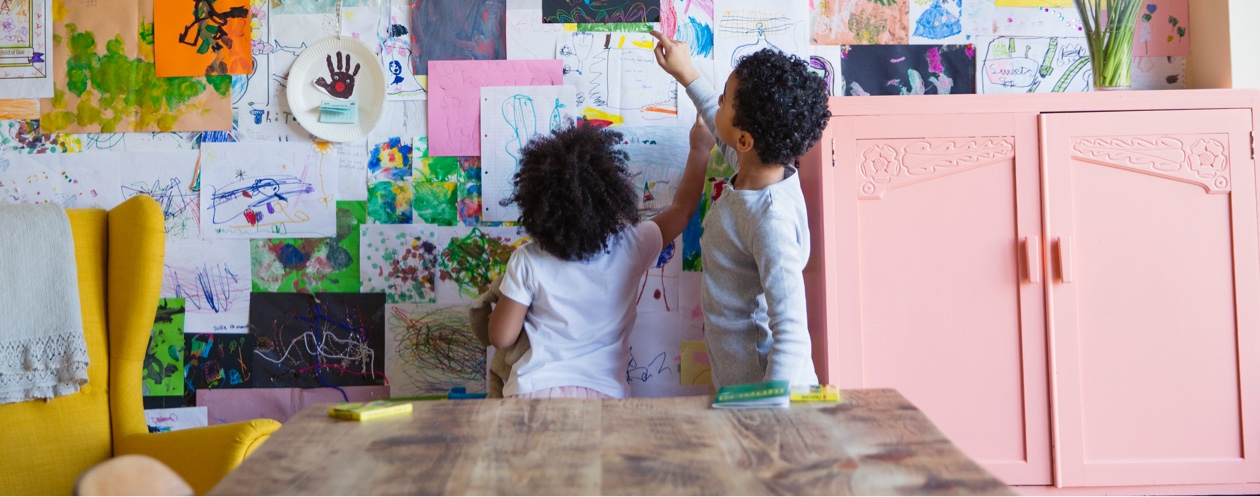 children admiring drawings pinned to wall
