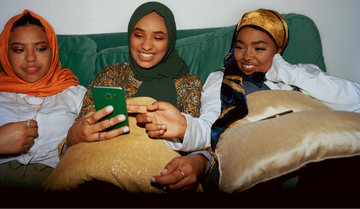 three females sitting on green sofa