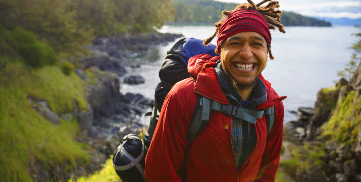 smiling man wearing red headband out hiking