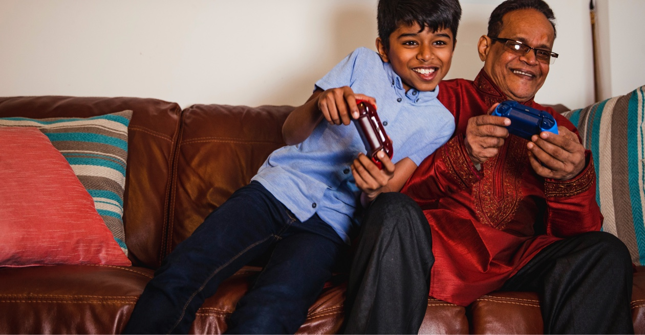 grandson and grandfather playing game console