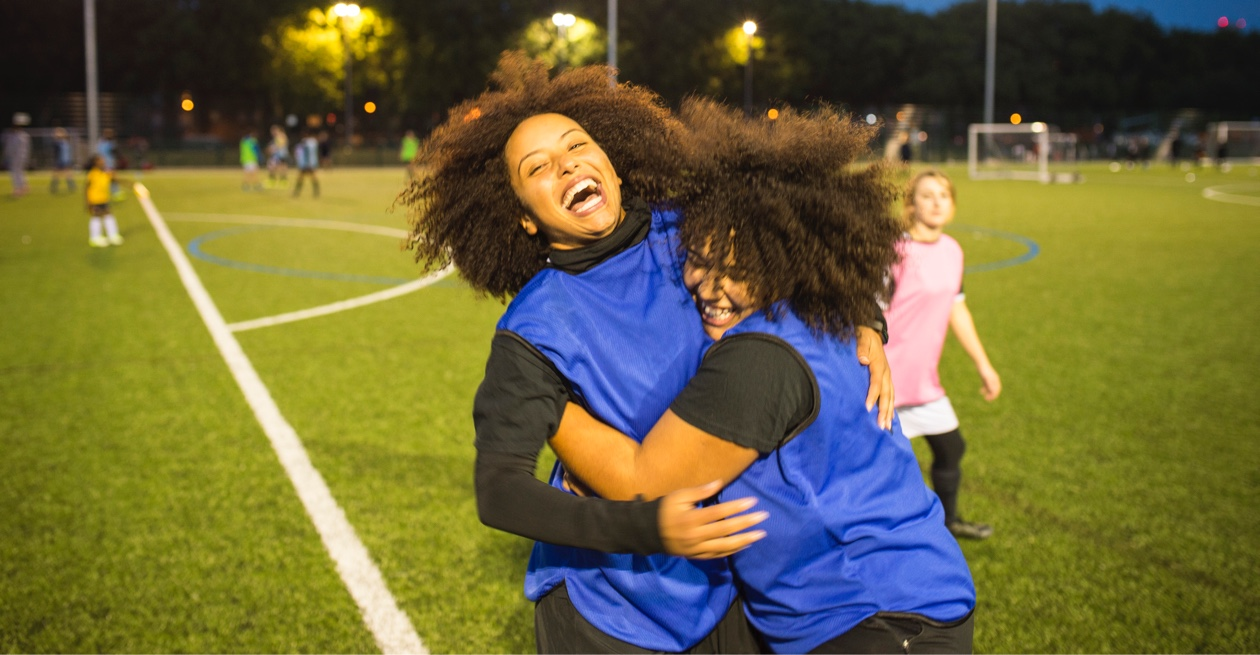 two girls hugging on football pitch