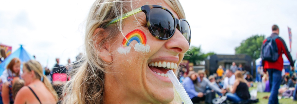 woman smiling with rainbow painted on cheek