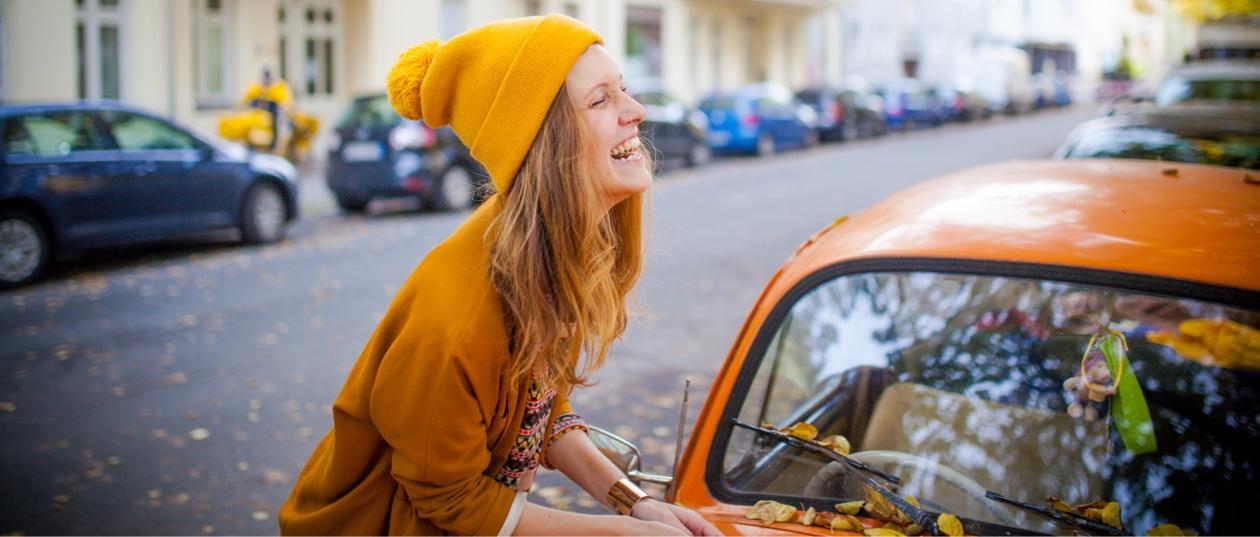 woman smiling wearing mustard hat