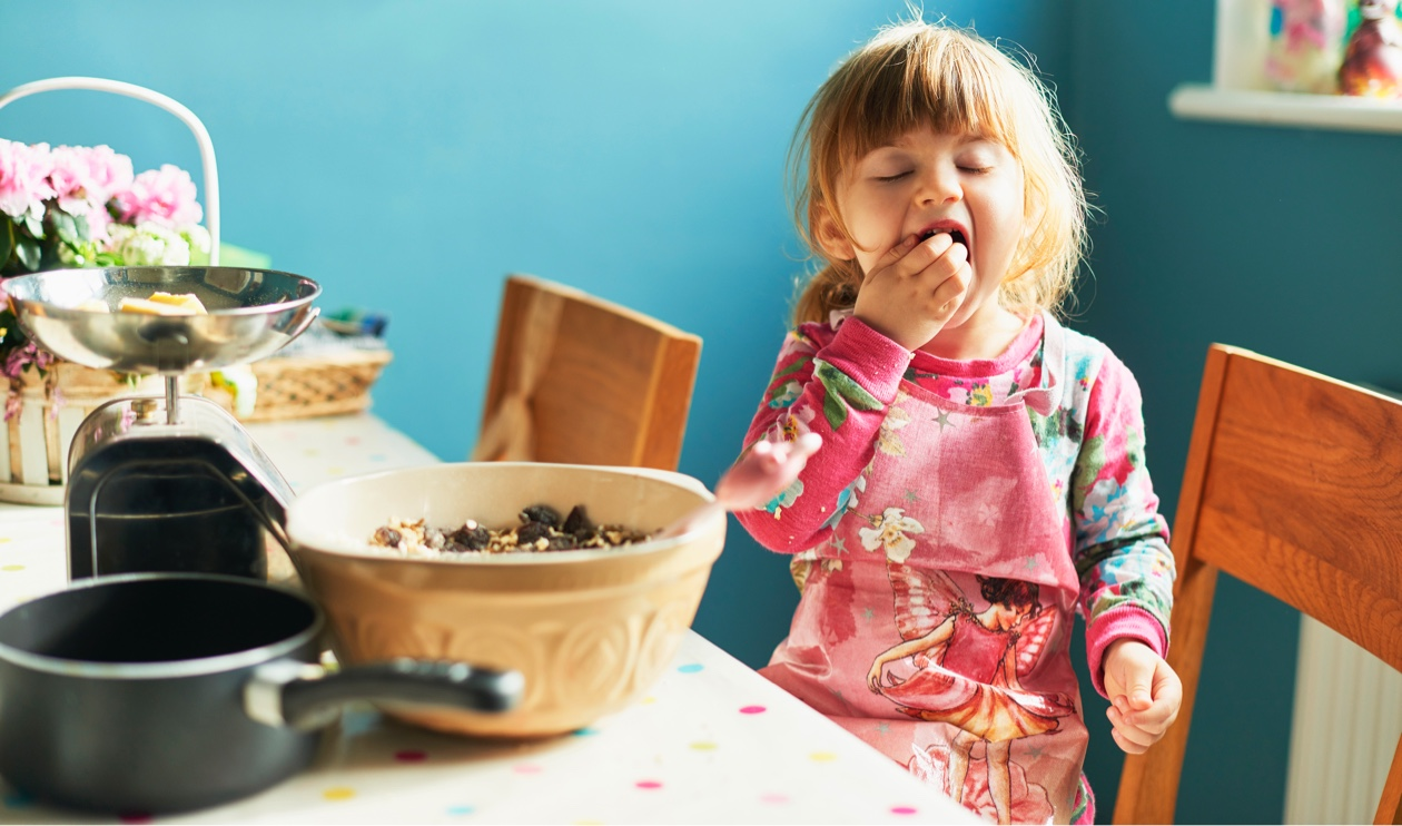 little girl eating from large mixing bowl