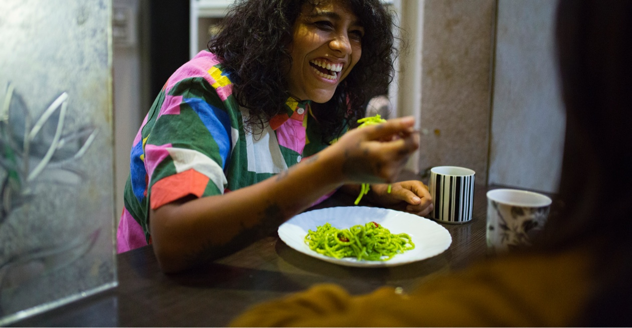 woman smiling and eating noodles