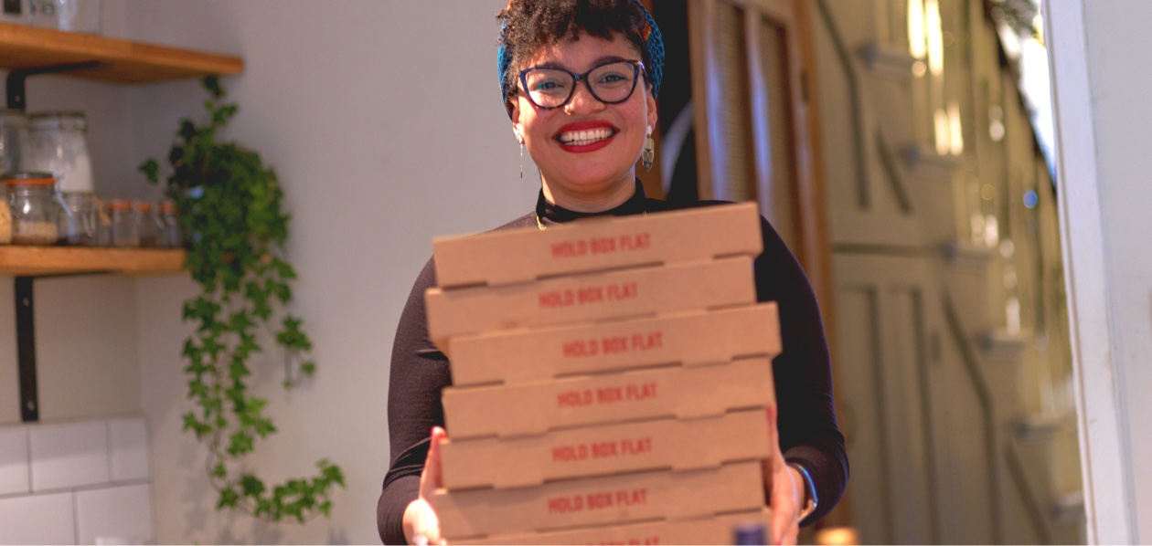 woman in glasses holding stack of pizza boxes