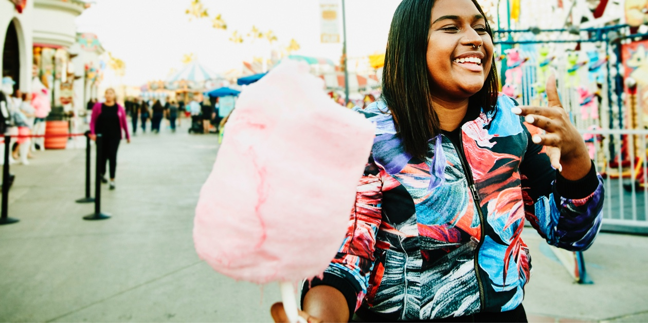 woman at theme park holding candy floss