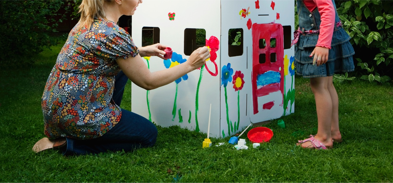 mother and daughter painting cardboard house in garden