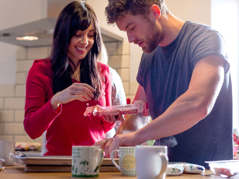 Two people in the kitchen with a cup of tea.