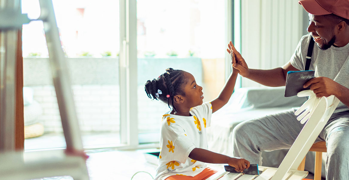 Man and a young girl high fiving in a living room