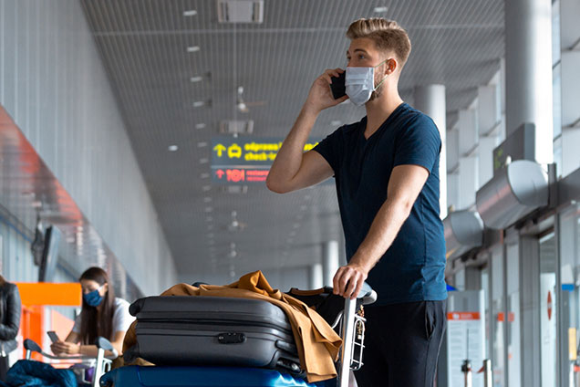 Man in an airport wearing a face mask