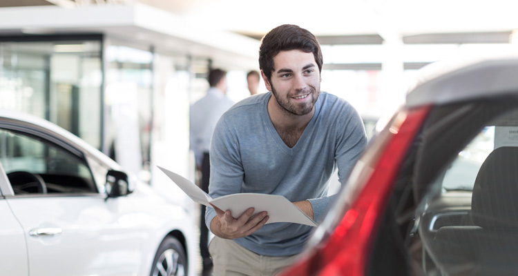 Man looking at a car in a showroom.