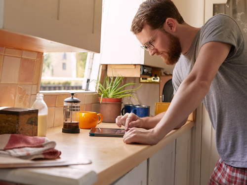 Man wearing pyjamas looking at his tablet on a kitchen counter.