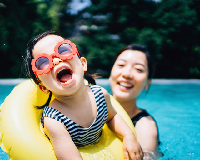 Mother and young daughter in pool