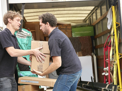 Two men loading a moving van. Helping each other with box.
