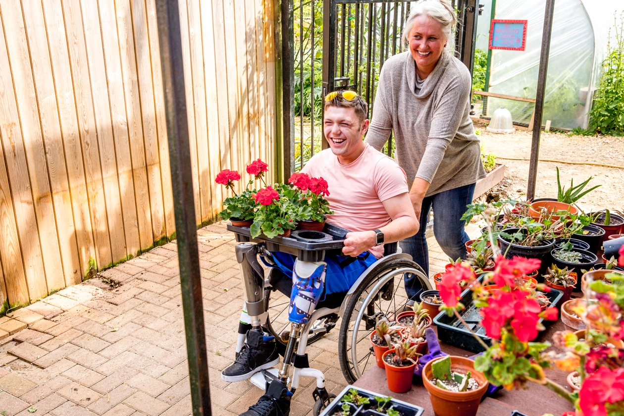 guy in wheelchairs with flowers while he is pushing by his mother