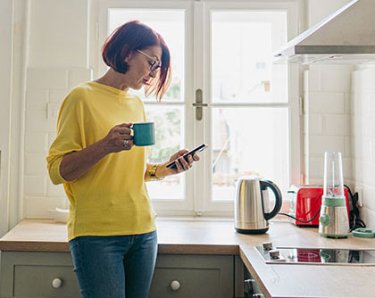 Woman checking her phone in the kitchen