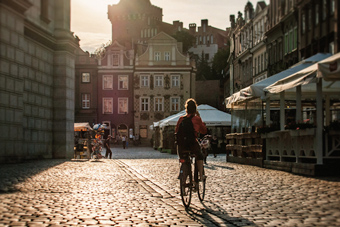 woman cycling through town square
