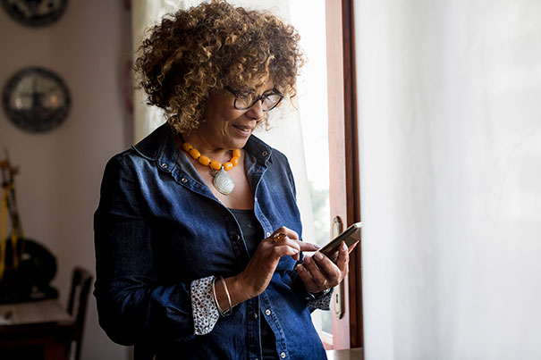 A woman with an orange necklace using our mobile app