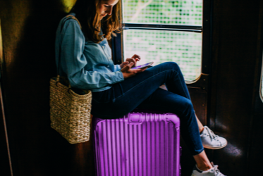 Travelling woman sitting on her suitcase