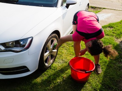 woman washing car tyre